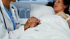 Doctor comforting pregnant woman in ward