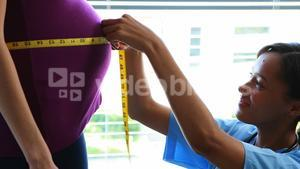 Doctor measuring pregnant womans belly in ward