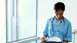 Female doctor looking at clipboard in corridor