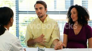 Couple talking to doctor in clinic