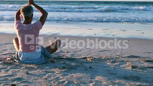 Senior woman doing yoga on the beach