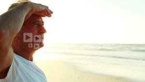 Smiling senior man standing on beach