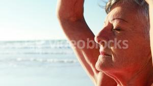 Senior woman doing yoga at beach