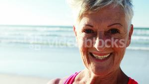 Smiling senior woman standing on beach