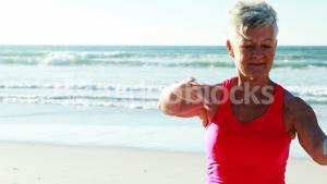 Senior woman doing exercise on beach