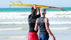 Senior couple carrying surfboard over head while walking on beach