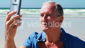 Senior man having video call on the mobile phone at the beach