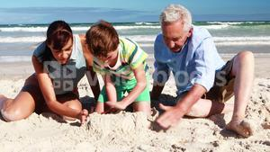 Happy family playing in sand at the beach