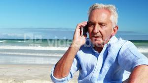 Senior man talking on mobile phone on the phone at the beach