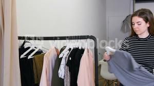 Female stylish selecting apparel from clothes rack