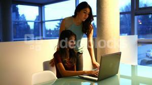 Female executives discussing over laptop at desk
